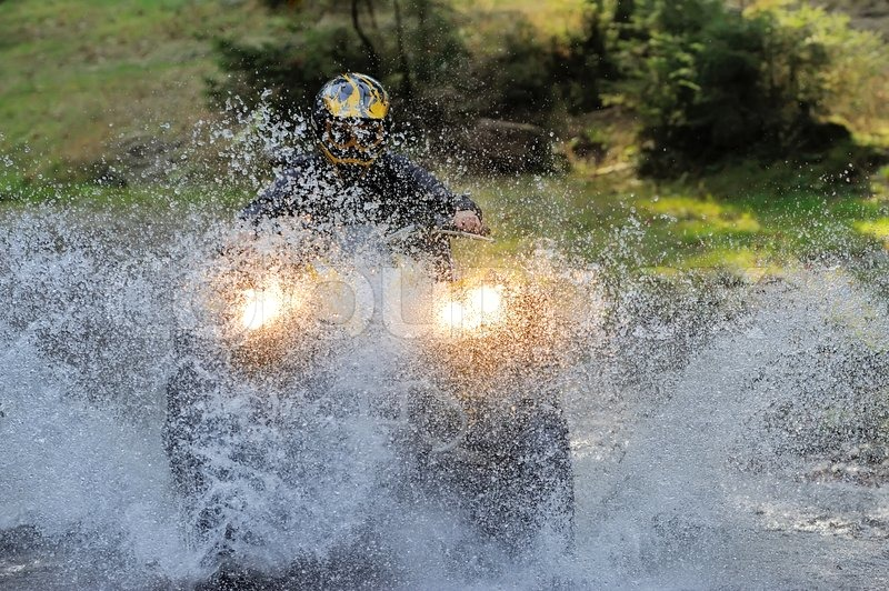 Travel on ATVs in river, stock photo