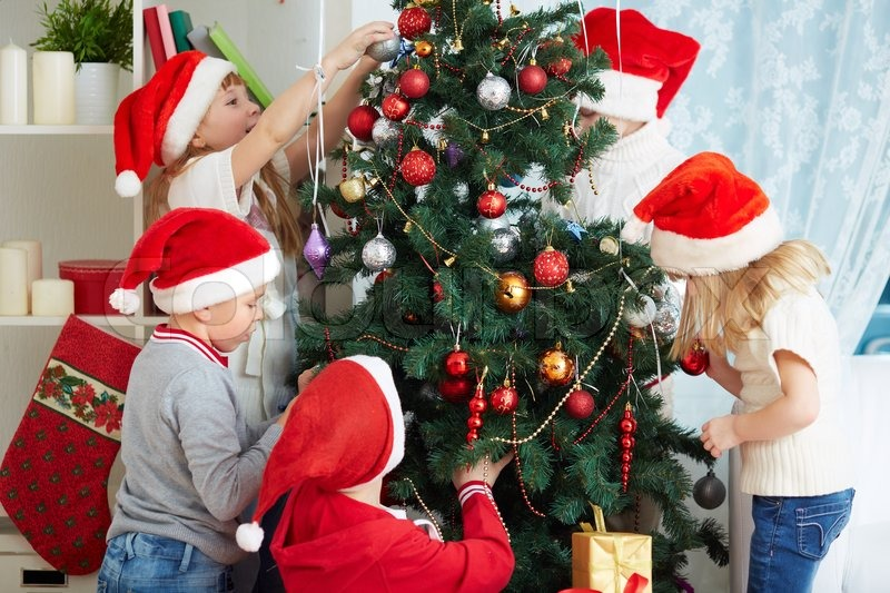 Group of adorable kids in Santa caps decorating xmas tree | Stock ...
