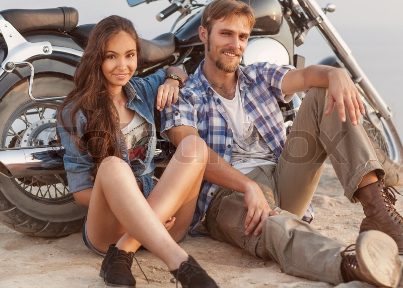 Two people and bike - fashion woman and man sitting by motorbike and resting. Adventure and vacations concept, stock photo