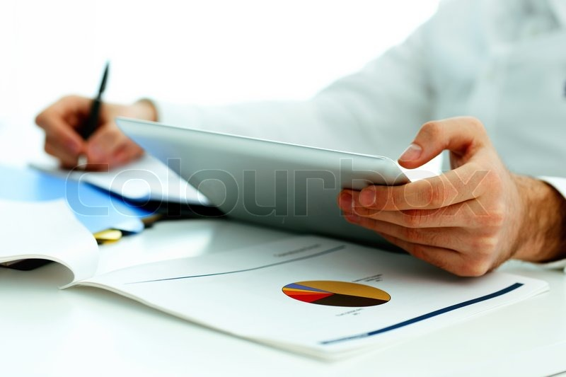 Closeup image of a man holding tablet computer and writing something down, stock photo