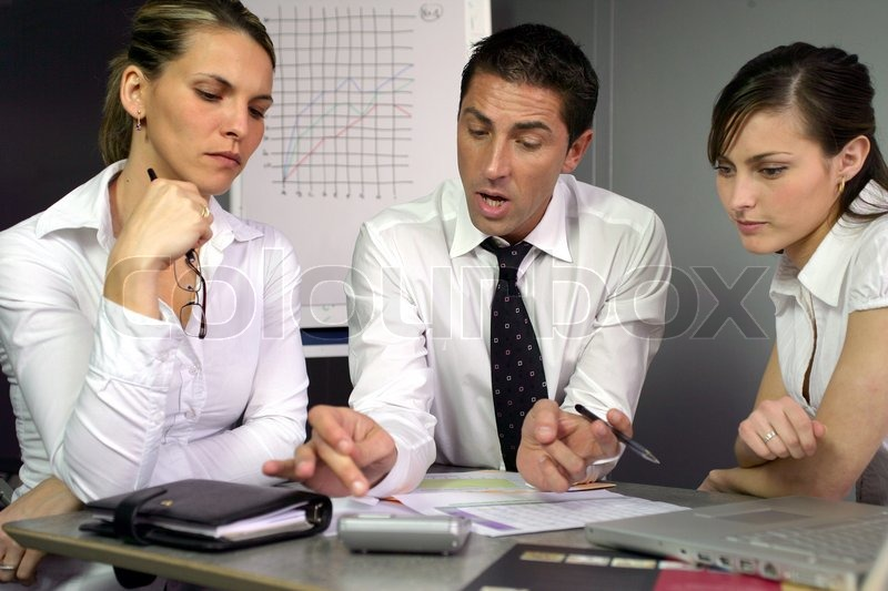 Businesspeople discussing performance, stock photo