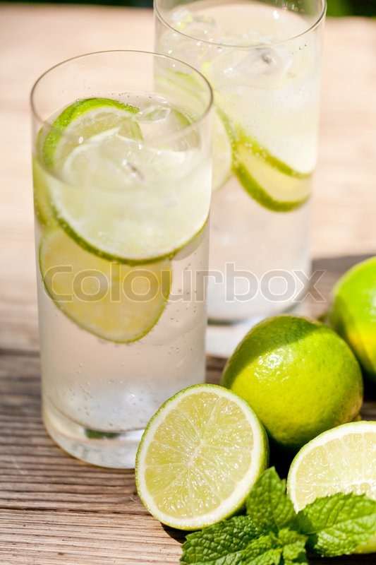 Fresh cold refreshment drink mineral water soda with lime and mint on wooden table in summer, stock photo