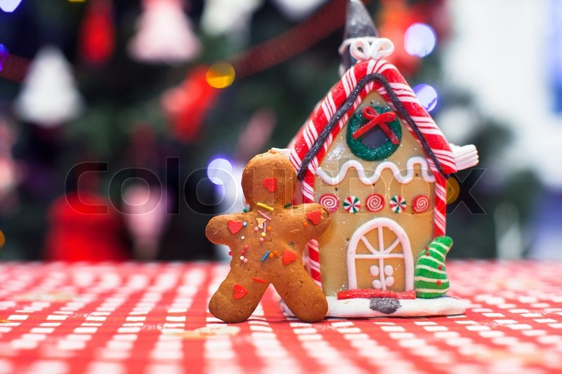 Cute Gingerbread Man In Front Of His Candy Ginger House