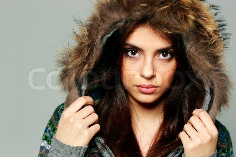 Closeup portrait of a young pensive woman in warm winter outfit on gray background, stock photo