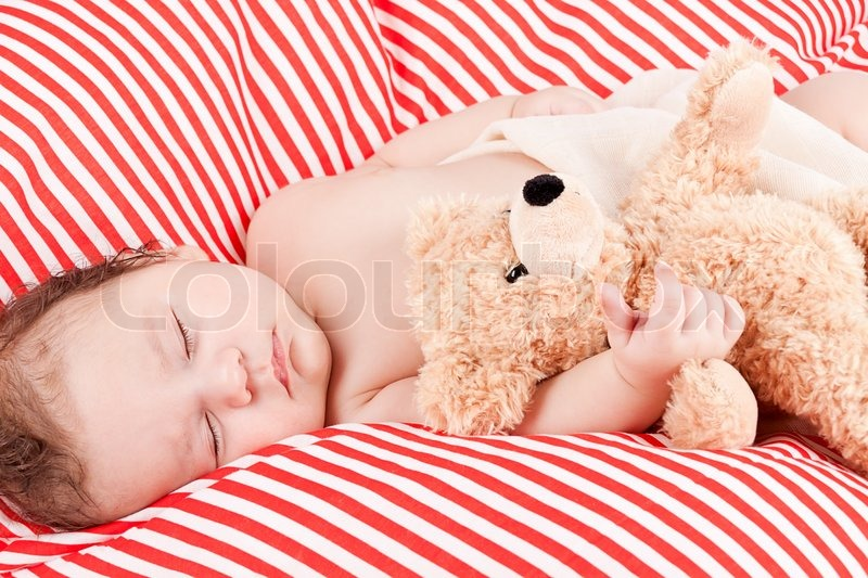 Sleeping cute little baby on red and white stripes pillow with teddy bear, stock photo