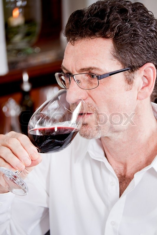 Man and woman in restaurant for dinner drinking red wine and smiling, stock photo