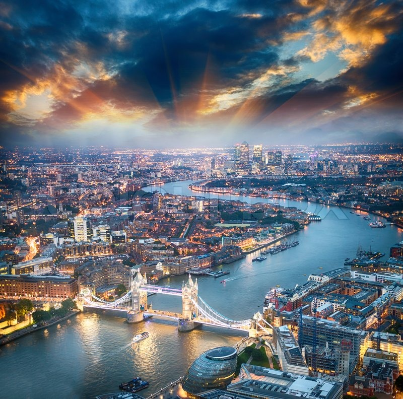 London. Aerial view of Tower Bridge at dusk with beautiful city skyline, stock photo