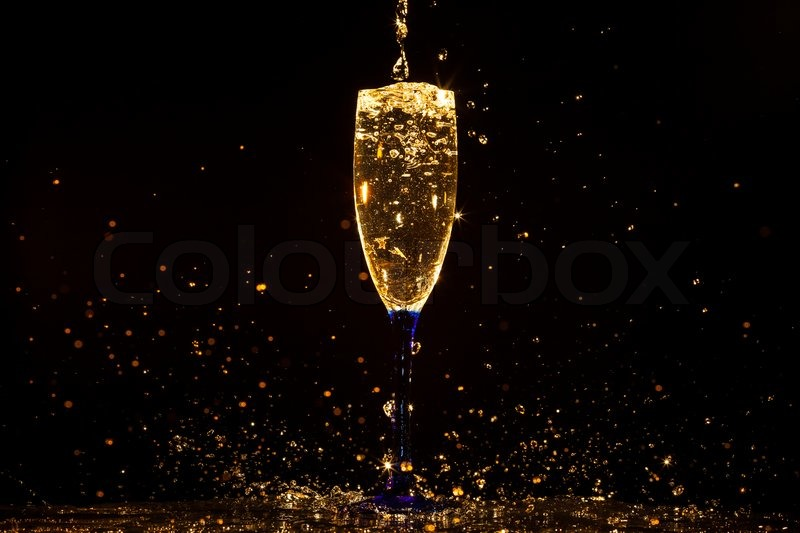 Champagne pouring in glass on a black background, stock photo