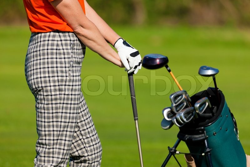 Mature Woman - only torso to be seen - with golf bag playing golf on a golf course, stock photo