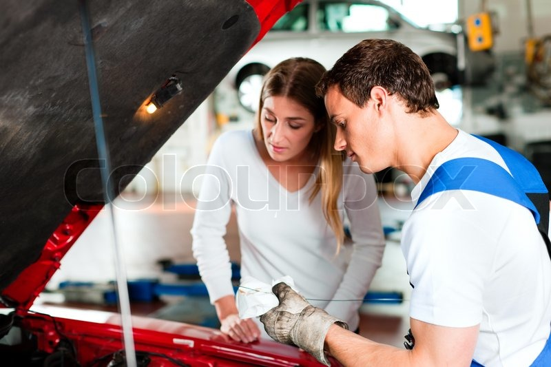 Woman talking to a car mechanic in his repair shop, both are standing next to the car, stock photo