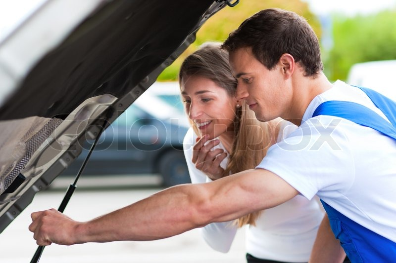 Woman talking to a car mechanic in a parking area, both are standing next to the car, stock photo