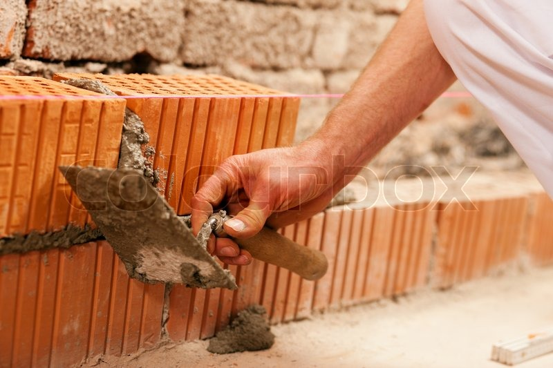Bricklayer laying, well, bricks to make a wall, he is pulling grout out of a joint with his trowel. This man is really working hard, stock photo
