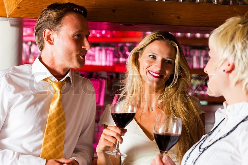 Man and two women in a hotel bar in the evening having glasses of red wine and probably a little flirt, stock photo