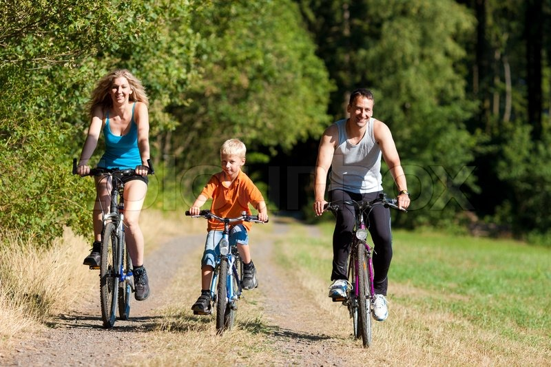 Family with child on their bikes on a summer day in sport outfit, they are exercising, stock photo