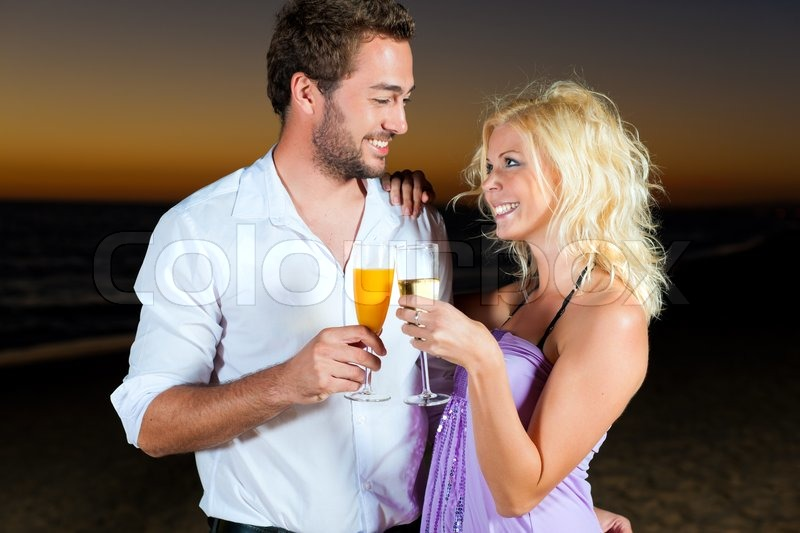Stock image of 'couple in the sunset, they are wearing smart casual clothes and drink champagne'