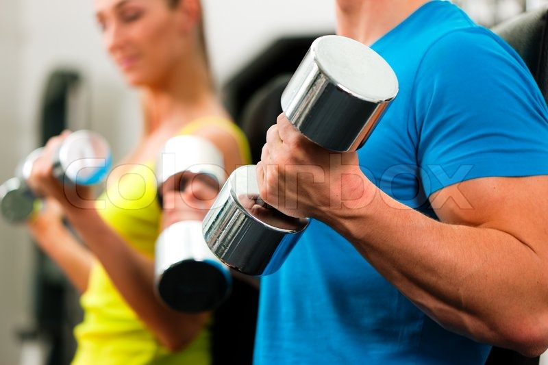 Couple in the gym, rivaling each other, exercising with dumbbells , stock photo