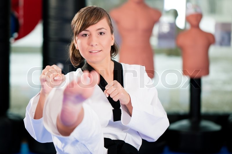Woman in martial art training in a gym, she is doing a taekwondo front kick, stock photo