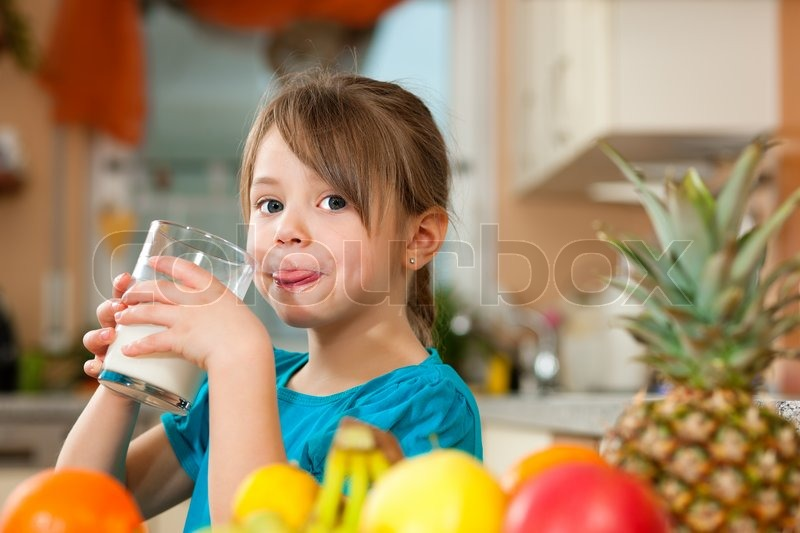 Healthy eating - Child drinking milk, lots of fresh fruit on the table in front, stock photo