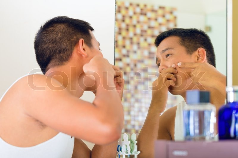 Asian man discovering a pimple in face, stock photo