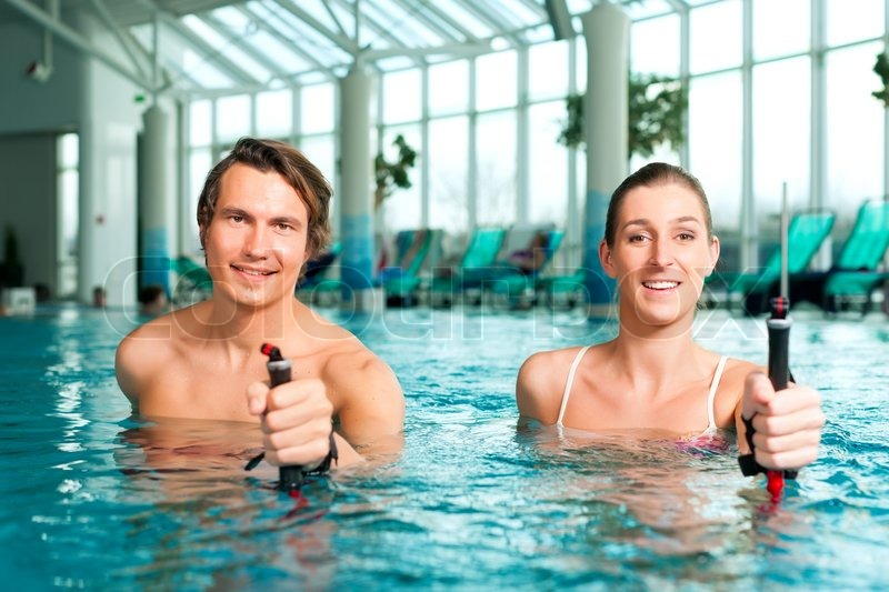 Fitness - a young couple (man and woman) doing sports and gymnastics or water aerobics under water in swimming pool or spa with Nordic walking sticks, stock photo