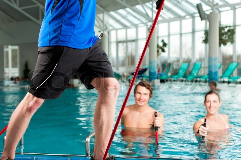 Fitness - a young couple - man and woman - doing sports and gymnastics or water aerobics under water in swimming pool or spa with Nordic walking sticks and trainer, stock photo