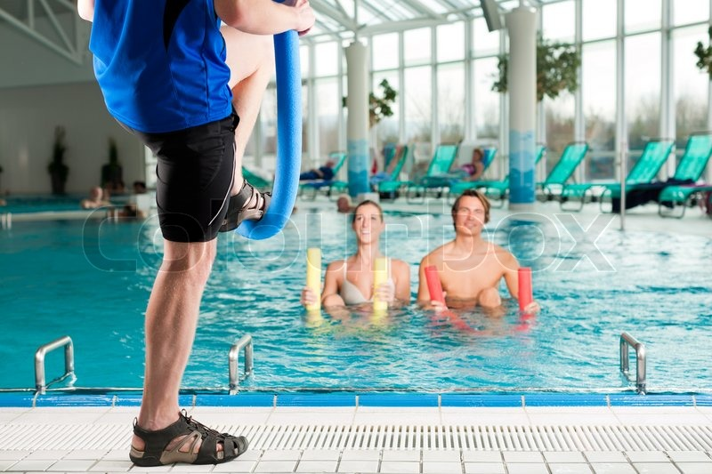 Fitness - a young couple - man and woman - doing sports and gymnastics or water aerobics under water in swimming pool or spa with swim noodle, stock photo