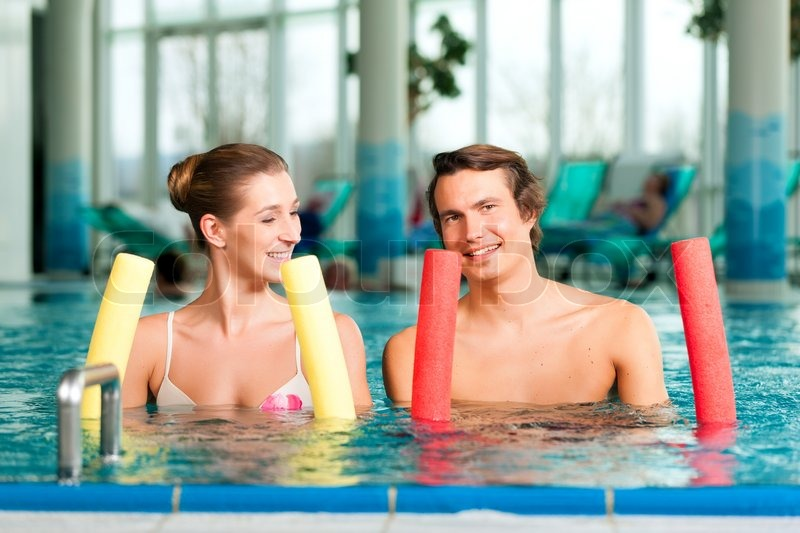 Fitness - a young couple (man and woman) doing sports and gymnastics or water aerobics under water in swimming pool or spa with swim noodle, stock photo