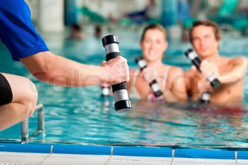 Fitness - a young couple (man and woman) doing sports and gymnastics or water aerobics under water in swimming pool or spa with dumbbells and instructor, stock photo