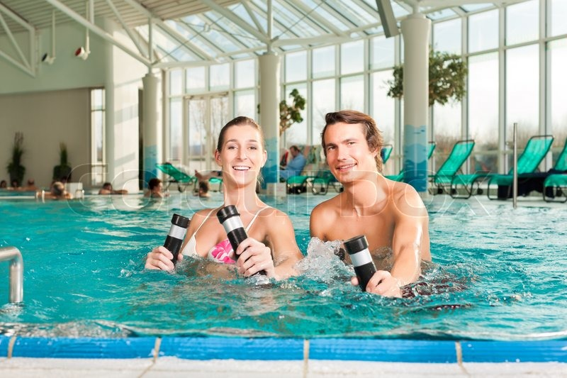 Fitness - a young couple - man and woman - doing sports and gymnastics or water aerobics under water in swimming pool or spa with dumbbells, stock photo