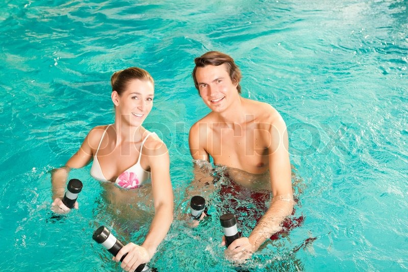 Fitness - a young couple (man and woman) doing sports and gymnastics or water aerobics under water in swimming pool or spa with dumbbells, stock photo
