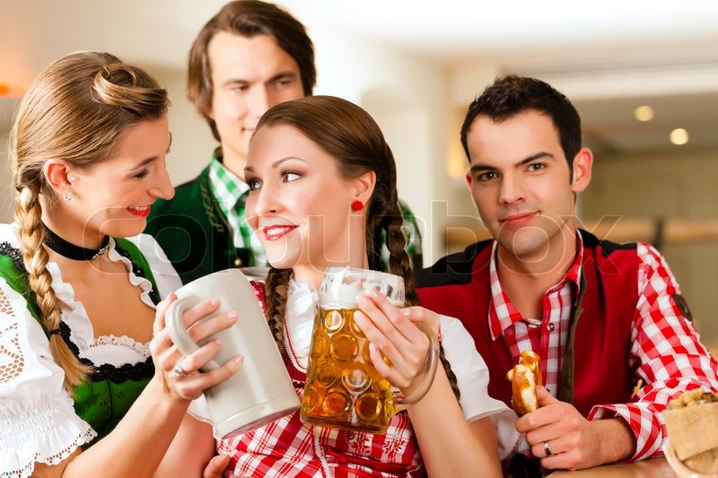 Young people in traditional Bavarian Tracht in restaurant or pub with beer and steins, stock photo
