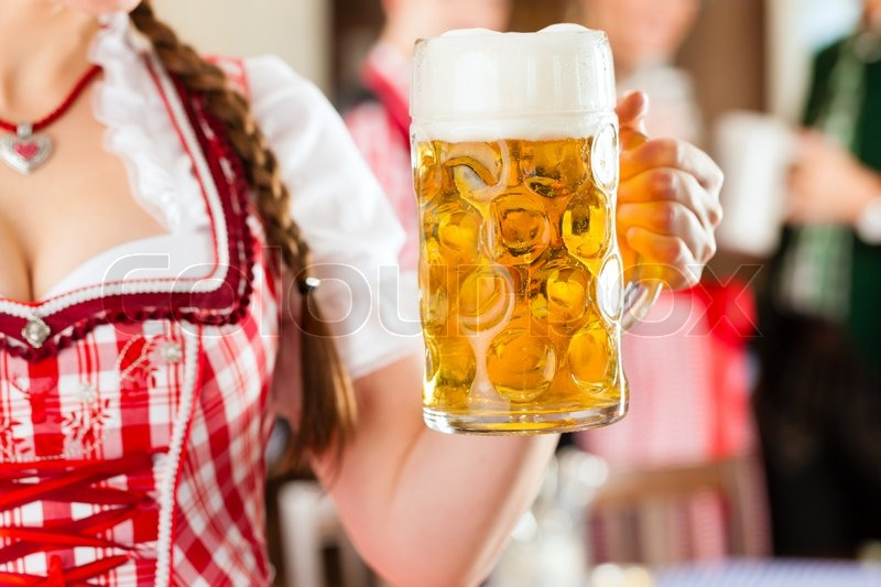 Young people in traditional Bavarian Tracht in restaurant or pub, one woman is standing with beer stein in front, the group in the background, stock photo