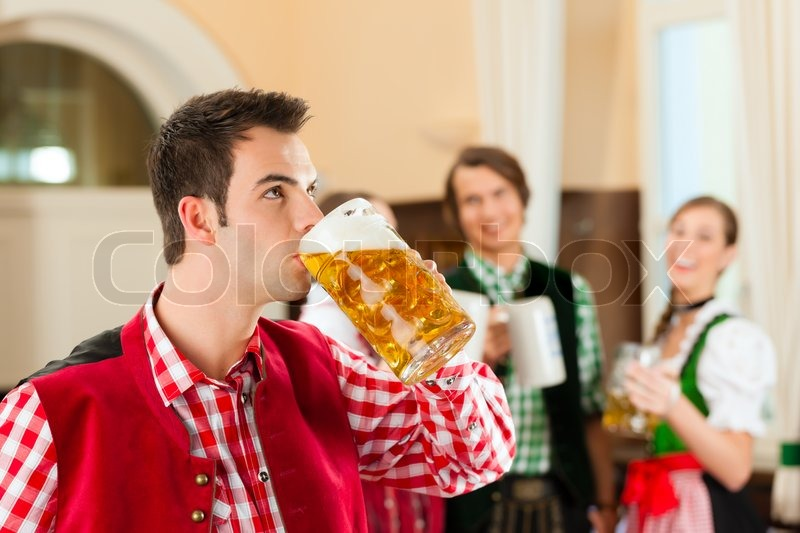 Young people in traditional Bavarian Tracht in restaurant or pub, one man is standing with beer stein in front, the group in the background, stock photo