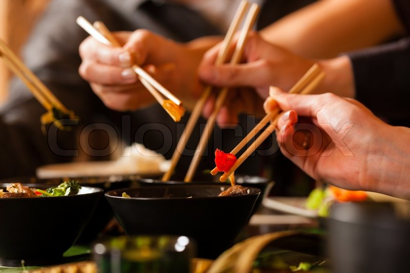 Young people eating in a Thai restaurant, they eating with chopsticks, close-up on hands and food, stock photo