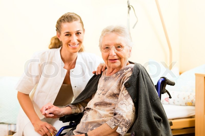 Young nurse and female senior in nursing home, the old lady sitting in a wheel chair, stock photo