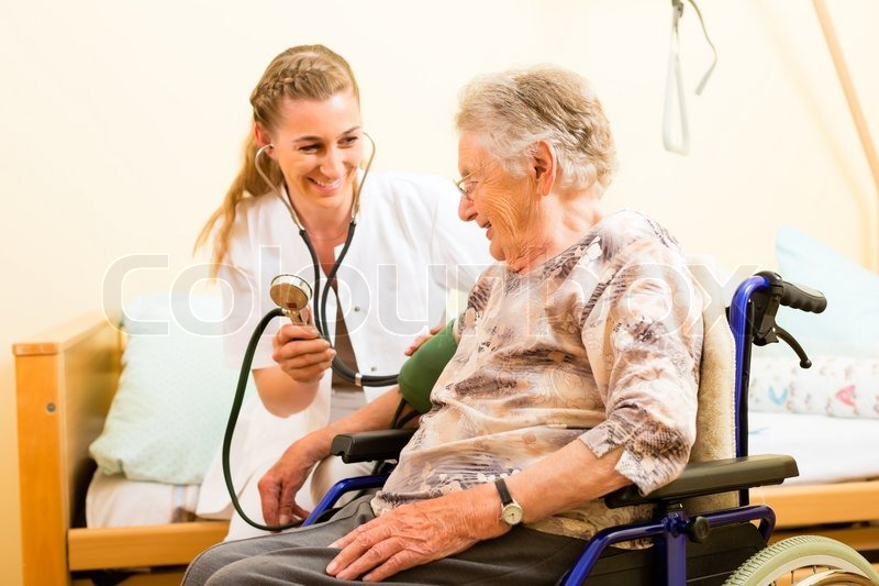 Stock image of 'Young nurse and female senior in nursing home, the blood pressure is going to be measured'