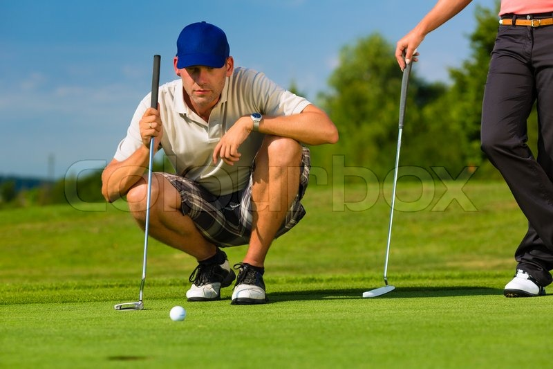 Young golf player on course putting, he aiming for his put shot, stock photo