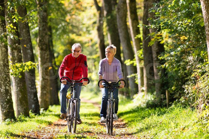 Stock image of 'Senior Man and woman exercising with bicycles outdoors, they are a couple'