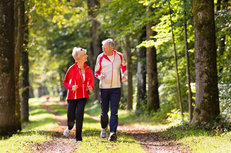 Senior Couple doing sport outdoors, jogging on a forest road in the autumn, stock photo