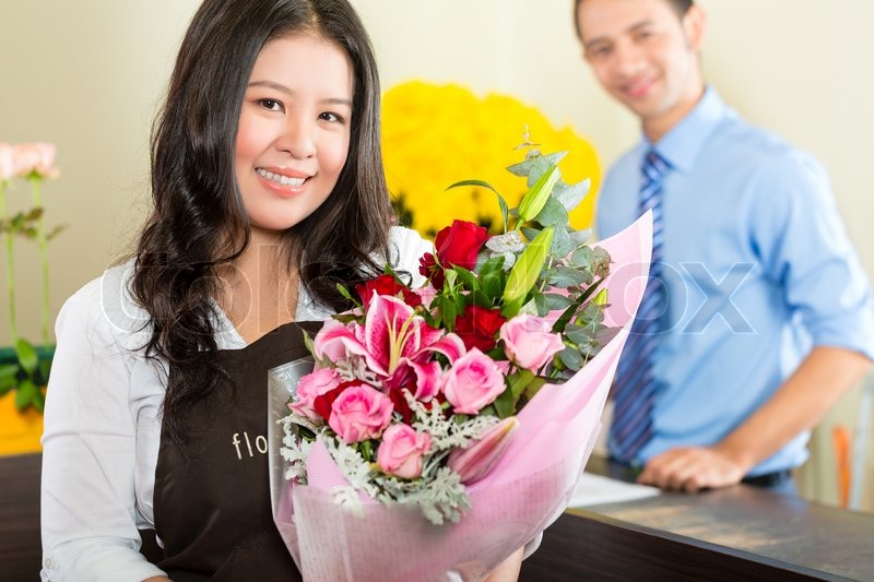 Friendly Asian florist or Saleswoman in a flower shop, holding a flower bouquet, stock photo