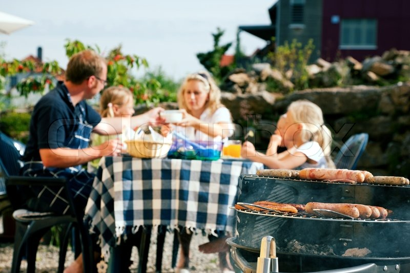 Stock image of 'Family having a barbecue in the garden, eating (focus on barbeque grill!)'
