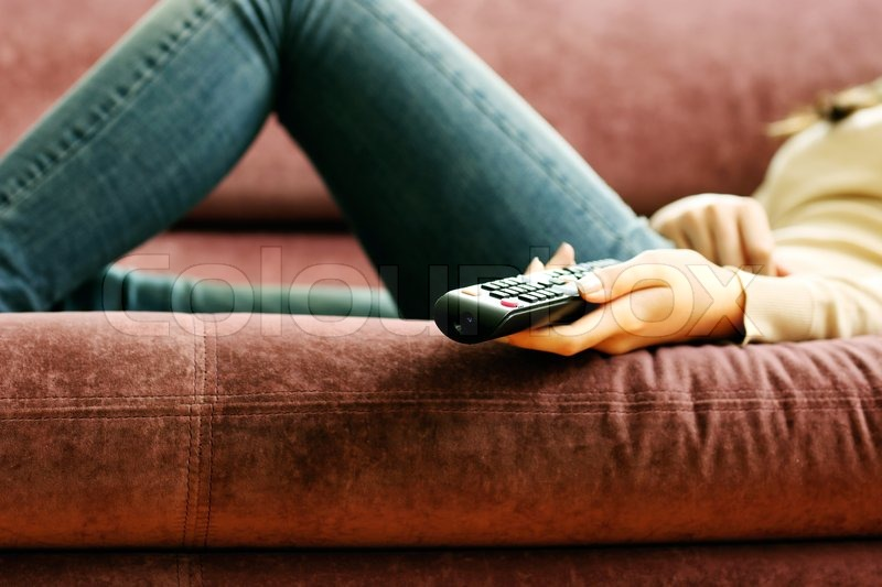Stock image of 'Closeup image of a female hand holding remote control'