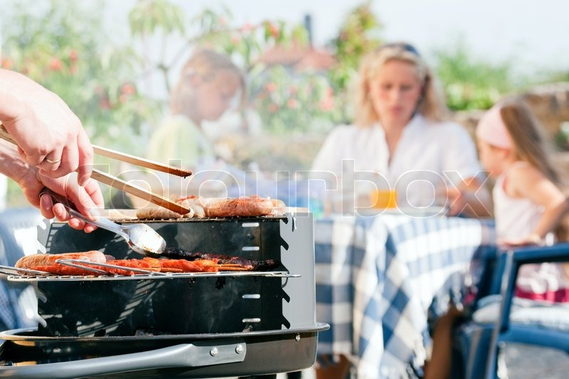 Stock image of 'Family having a barbecue in the garden - focus on cooking in the foreground'