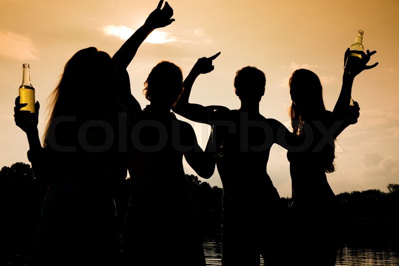 Stock image of 'People (two couples) on the beach dancing to music, drinking and having a lot of fun in the sunset - only silhouette of people to be seen'