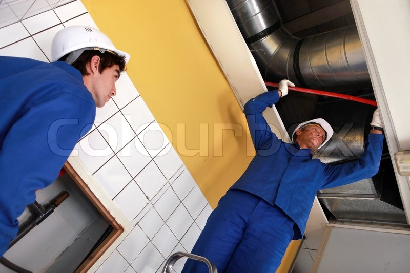 Workers working on air conditioning, stock photo