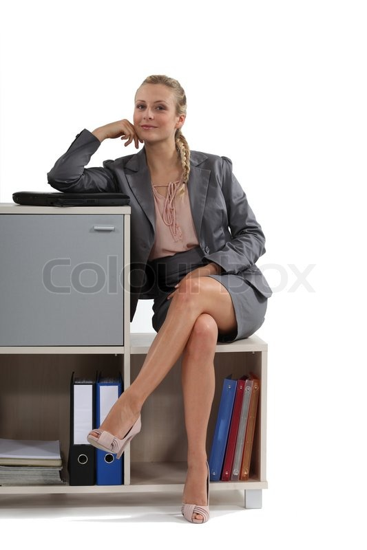 Businesswoman Sitting By Storage Unit Stock Photo
