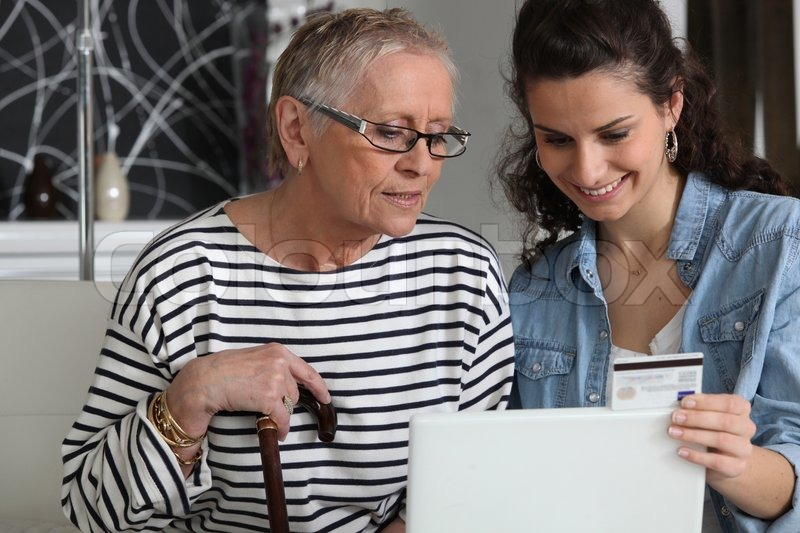 Stock image of 'Grandma and home helper with laptop'