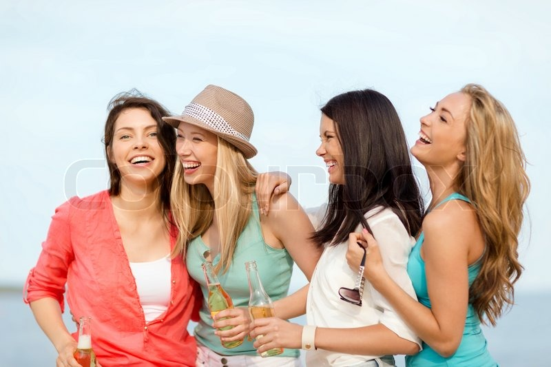 Summer holidays and vacation concept - smiling girls with drinks on the beach, stock photo
