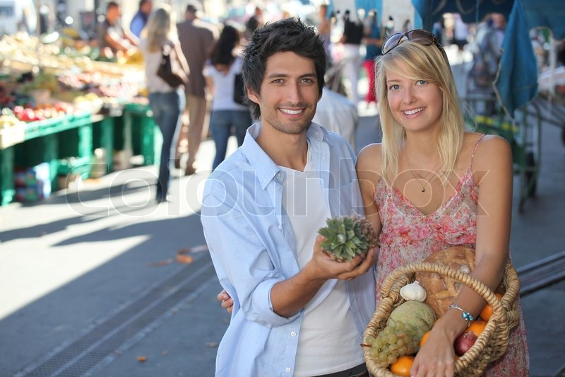 Young couple with a basket of fruit in a busy marketplace, stock photo
