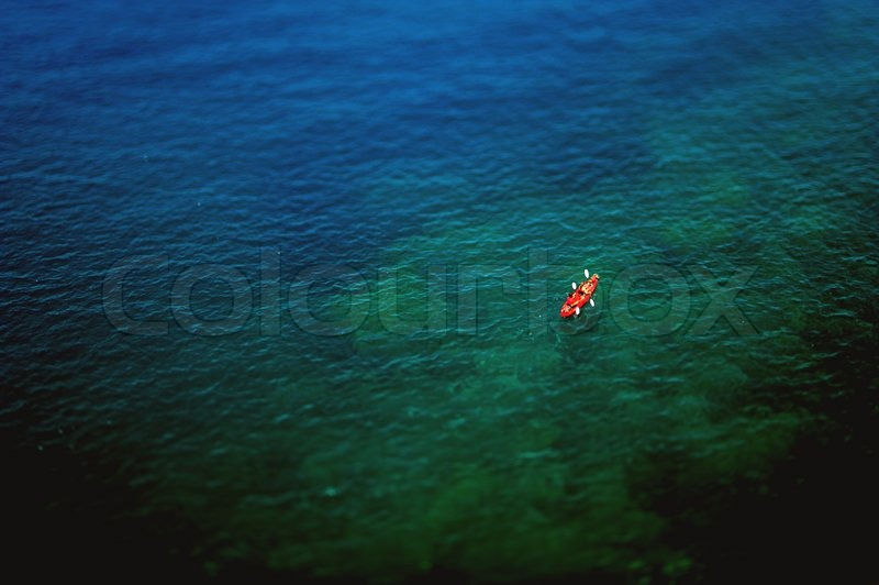 Couple kayaking in wide blue sea as seen from above. Tilt-shift lens used, stock photo